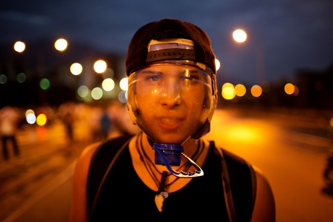 In this Feb. 18, 2014, an anti-government demonstrator wears a hand made mask from a water bottle to protect against the effects of tear gas during clashes with security forces at an anti-government protest in Caracas, Venezuela. The eye-catching transparent mask made from a large plastic water bottle is now so popular that several videos demonstrating its assembly are circulating online.