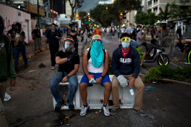 In this March 2, 2014 photo, anti-government demonstrators take a break on an old refrigerator used to build a barricade during clashes with security forces in Caracas, Venezuela. Fashion is not foreign to the young demonstrators who skirmish nearly nightly with security forces at the barricades in the Venezuelan capital. Painter and dust masks are common protection against tear gas, as are ski, scuba and swim goggles.