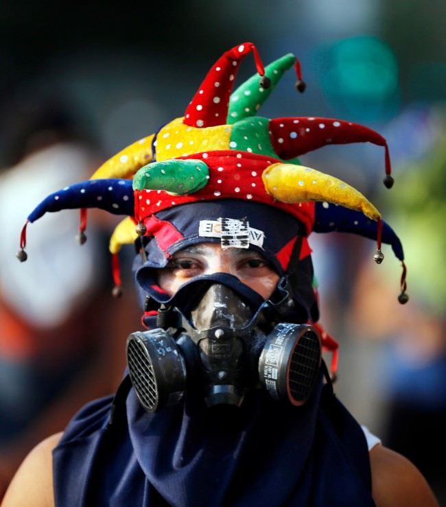 In this March 4, 2014 photo, an anti-government demonstrator wears a joker hat and painters mask to protect from the effects of tear gas during clashes with security forces in Plaza Altamira, Caracas, Venezuela. As the protests against Venezuela's socialist-led government move into their second month, front-line head gear includes skate, bicycle and motorcycle helmets but encompasses the more whimsical, too.