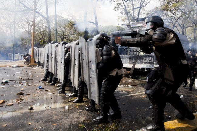 A Bolivarian National Police officer fires a tear gas grenade at demonstrators during clashes at an antigovernment protests in Caracas, Venezuela, Wednesday, March 12, 2014. According to local authorities, several deaths have been reported and a number of others, including National Guardsmen, have been wounded after being shot by unknown assailants in separate incidents in the central Venezuelan city of Valencia.