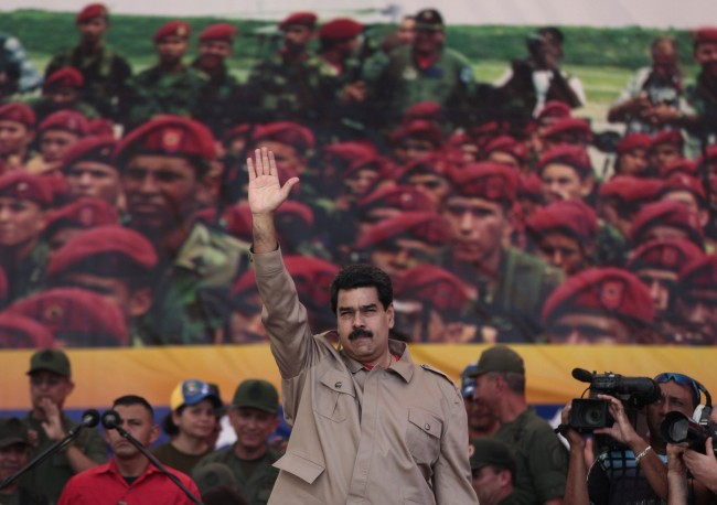 Venezuela's President Nicolas Maduro waves to supporters during a march in honor of Venezuela's Army and National Guard, in Caracas, Venezuela, Saturday, March 15, 2014. The Venezuelan government is stepping up security operations in Caracas and other cities where demonstrators are blocking streets, avenues and highways. Maduro said that those involved in creating road barricades will be arrested.