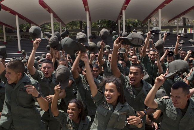 Venezuelan soldiers shout slogans in support of President Nicolas Maduro during a march in honor of Venezuela's Army and National Guard, in Caracas, Venezuela, Saturday, March 15, 2014. The Venezuelan government is stepping up security operations in Caracas and other cities where demonstrators are blocking streets, avenues and highways. Maduro said that those involved in creating road barricades will be arrested