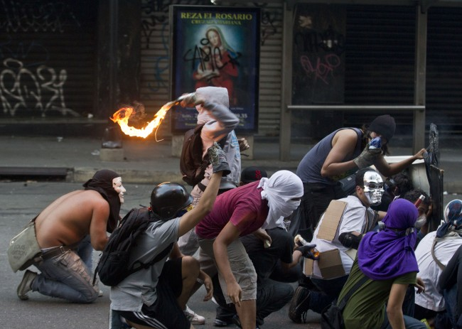 A hooded protester throws a Molotov cocktail towards Bolivarian National Police during clashes in Caracas, Venezuela, Saturday, March 15, 2014. Anti-government street protests by Venezuelans fed up with soaring inflation, violent crime and shortages of basic items such as flour and cooking oil have roiled Venezuela for more than a month. The Venezuelan government says at least 25 people have died in the turmoil since Feb. 12.