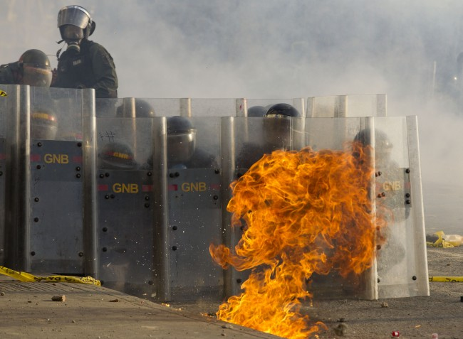 Bolivarian National Guard soldiers take cover behind their shields as a molotov cocktail lands during clashes near Plaza Altamira in Caracas, Venezuela, Sunday, March 16, 2014. Anti-government street protests by Venezuelans fed up with violent crime, shortages of basic items such as flour and cooking oil and high inflation have roiled Venezuela for more than a month.