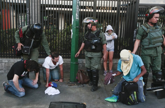 Anti-government demonstrators kneel as they are arrested by Bolivarian National Guards during clashes near Plaza Altamira in Caracas, Venezuela, Sunday, March 16, 2014. The protester standing behind was also arrested. Anti-government street protests by Venezuelans fed up with violent crime, shortages of basic items such as flour and cooking oil and high inflation have roiled Venezuela for more than a month.