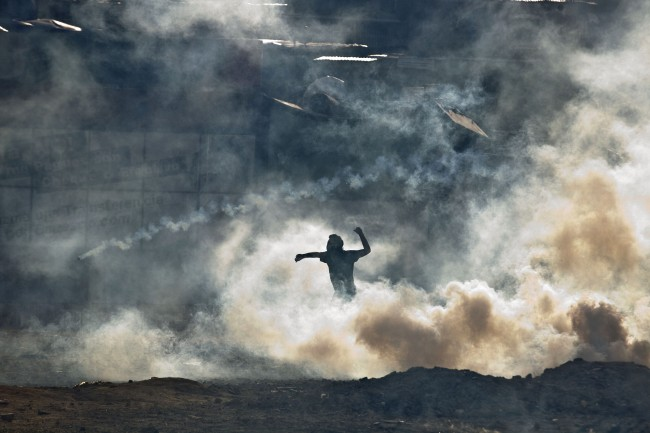 An anti-government demonstrator standing in teargas fired by Bolivarian National Guards prepares to throw a rock during clashes near Plaza Altamira in Caracas, Venezuela, Sunday, March 16, 2014.