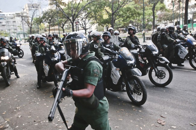 A Bolivarian National Guard aims his weapon in search of anti-government demonstrators after dispersing them from Plaza Altamira in Caracas, Venezuela, Sunday, March 16, 2014.