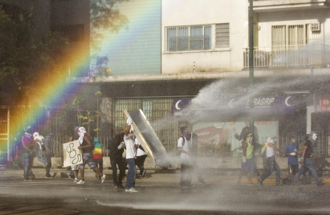 Masked anti-government demonstrators use improvised shields to take cover from a water cannon fired by Bolivarian National Police during clashes near Plaza Altamira in Caracas, Venezuela, Sunday, March 16, 2014.
