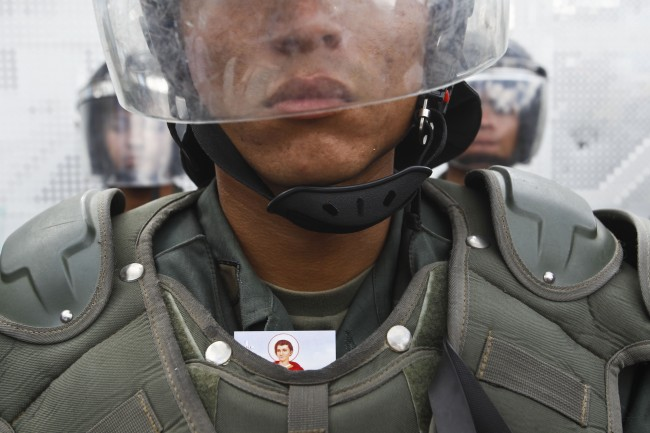 A religious image is tucked behind the body armor of a Bolivarian National Guard on duty during an anti-government march in Caracas, Venezuela on Sunday, March 16, 201