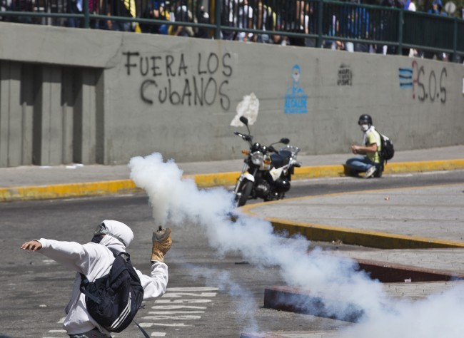 A masked protester returns a tear gas canister fired by Bolivarian National Police, in Caracas, Venezuela, Thursday, March 20, 2014. Thursday dawned with two more opposition politicians, San Cristobal Mayor Daniel Ceballos and San Diego Mayor Enzo Scarano, behind bars. Police used tear gas and water cannons to disperse a student-called protest of several thousand people in Caracas, some of those demonstrating against the arrests of the mayors.