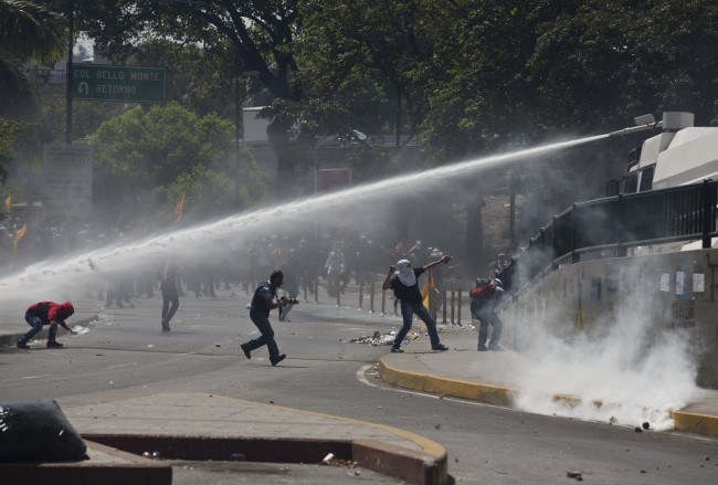 A water canon operated by Bolivarian National Police, sprays at protesters in Caracas, Venezuela, Thursday, March 20, 2014. Thursday dawned with two more opposition politicians, San Cristobal Mayor Daniel Ceballos and San Diego Mayor Enzo Scarano, behind bars. Police used tear gas and water cannons to disperse a student-called protest of several thousand people in Caracas, some of those demonstrating against the arrests of the mayors.