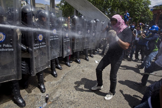 A Bolivarian National Police officer sprays an anti-government demonstrator with pepper spray during clashes at the Central University of Venezuela, UCV, in Caracas, Venezuela, Thursday, March 20, 2014.