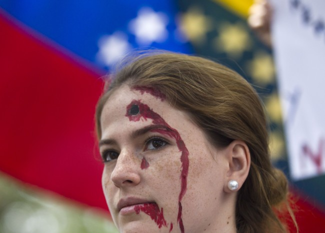 An anti-government demonstrator, with a bleeding bullet hole drawn on her forehead, takes part in a protest in front of an office of the Organization of American States, OAS, in Caracas, Venezuela, Friday, March 21, 2014. Opposition lawmaker Maria Corina Machado is scheduled to speak before the OAS council in a closed-door session Friday in Washington D.C., presenting the situation in her country where at least 28 people have been killed in daily anti-government protests that began in early February.