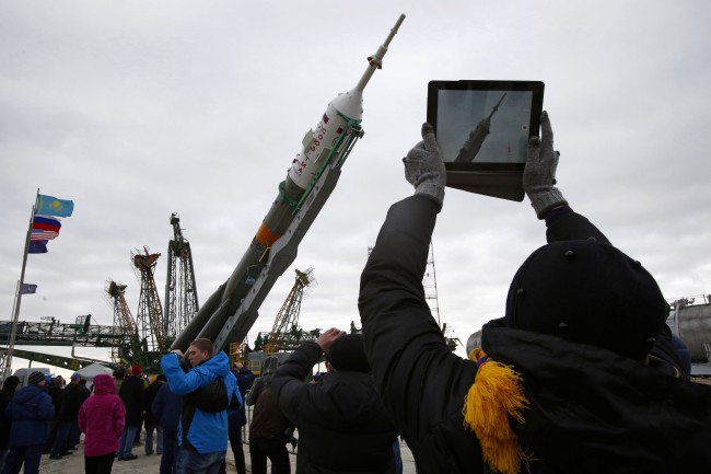 People take photos of Russia's Soyuz-FG booster rocket with the space capsule Soyuz TMA-12M