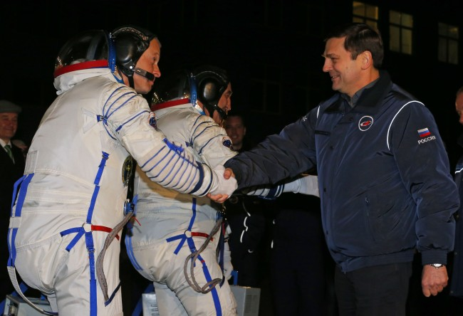 Oleg Ostapenko, right, head of the Russian Federal Space Agency, or Roscosmos, shakes hands with U.S. astronaut Steven