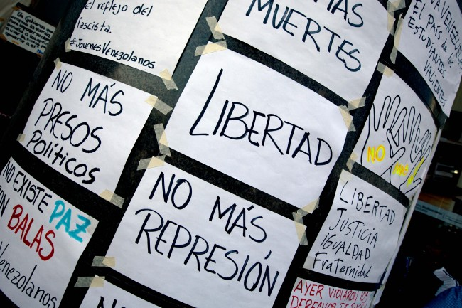 "Hand made posters are pasted on the wall outside of United Nations office in Caracas, Venezuela, Tuesday, March 25, 2014. The posters read in Spanish ""Freedom"", ""No more repression"", ""No more political prisoners"", ""No more killed"". A large group of protesting anti-government students have camped in front of the office of the United Nations asking it to come and observe the situation, as Venezuela's bloody political standoff heads into its third month. The decision to pitch tents on the concrete sidewalk along one of Caracas' busiest, smog-filled streets comes as foreign ministers from several South American nations arrive Tuesday to lend support to President Nicolas Maduro's efforts at reconciliation with his opponents"