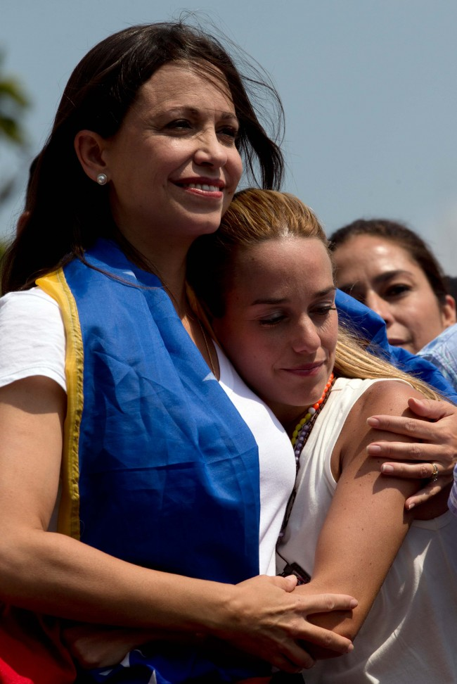 Leading opposition politician Maria Corina Machado, left, embraces Lilian Tintori, wife of jailed opposition leader Leopoldo Lopez, during a rally in Caracas, Venezuela, Wednesday, March 26, 2014. The head of Venezuela's congress, Diosdado Cabello, said Monday that Machado, who was stripped of her parliament seat, violated the constitution by addressing the Organization of American States last week at the invitation of Panama, which ceded its seat at the Washington-based group group so she could provide regional diplomats with a firsthand account of the unrest.