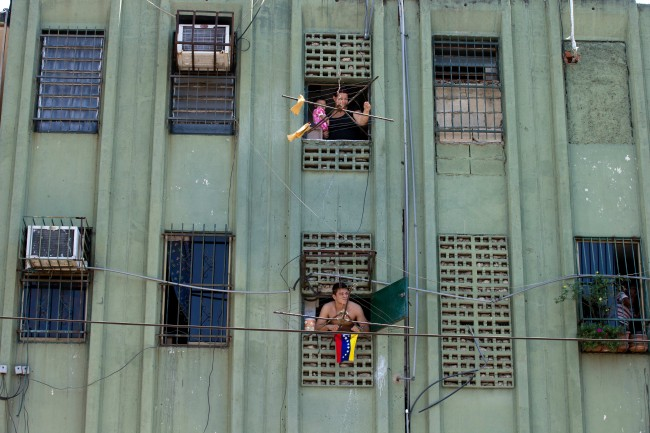 In this photo taken on Saturday, March 15, 2014. Residents look out from their apartments at a opposition protest at Isabelica neighborhood outside Valencia , Venezuela. The people of the poor district of La Isabelica were made to pay for taking to the streets in anti-government protests. More than a dozen masked men on motorcycles roared through, shooting up a barricade and killing a university student and a 42-year-old man painting his house.