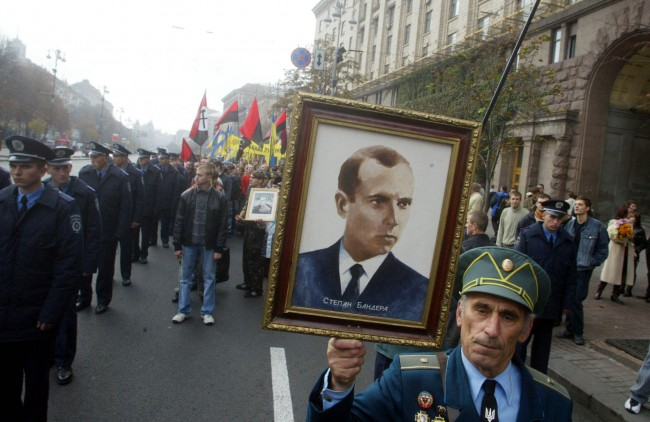 A partisan veteran from the Ukrainian Insurgent Army carries a portrait of Ukrainian Insurgent Army leader Stepan Bandera during a march in Kiev. Ukraine, Saturday, Oct. 15, 2005. The supporters of the Red Army veterans were rallying to protest against calls by Ukrainian partisans to receive official recognition as World War II veterans. The partisans from the Ukrainian Insurgent Army fought against both Nazis and Red Army soldiers during World War II in a bid to create an independent Ukraine. (AP Photo/Efrem Lukatsky)