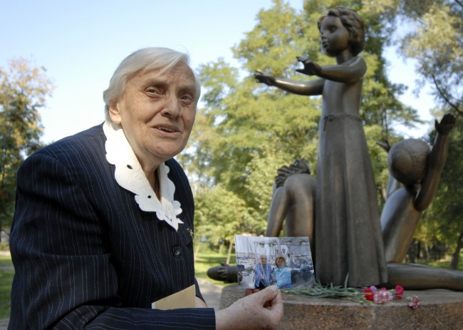 "Olga Rozhchenko, 82, shows a recent photo of a herself with Jewish woman, Manya Palti, right, who Rozhchenko saved during the Nazi occupation of Ukraine, Kiev, Tuesday, Sept. 26, 2006, with a monument commemorating children killed by Nazi in Baby Yar ravine. For 48 hours Sept. 29, 1941, the Nazis gunned down at least 33,771 Jews. Ukraine is preparing to mark the 65th anniversary of the Babi Yar massacre _ which Jewish leaders call a grim foreshadow of the Nazi's ""final solution"" which killed six million European Jews (AP Photo/Sergei Chuzavkov)"