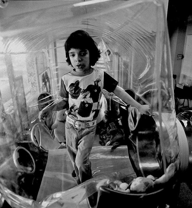 """David Vetter poses inside of his bubble in his Houston home in this Dec. 17, 1976 file photo. Vetter was born with a genetic disorder leaving him no natural immunities against disease. The disorder, known as Severe Combined Immune Deficiency Syndrome (SCID), became known as """"Bubble boy Disease"""", so named because of Vetter. (AP Photo/File)"""