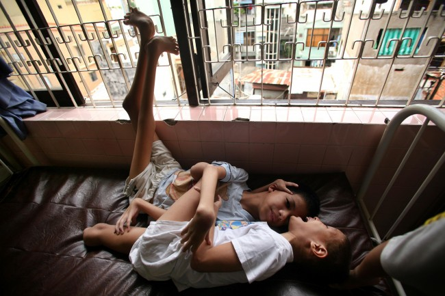 "Trien Meng Hiep, 9, against wall, is hugged by another boy at a ""Peace Village"" center in Tu Du hospital in Ho Chi Minh City, Vietnam on Friday, May 25, 2007. Both of the boys were born with severe physical deformities typical of spina bifida and which hospital officials suspect to have been caused by their parents exposure to dioxin in the chemical defoliant Agent Orange."