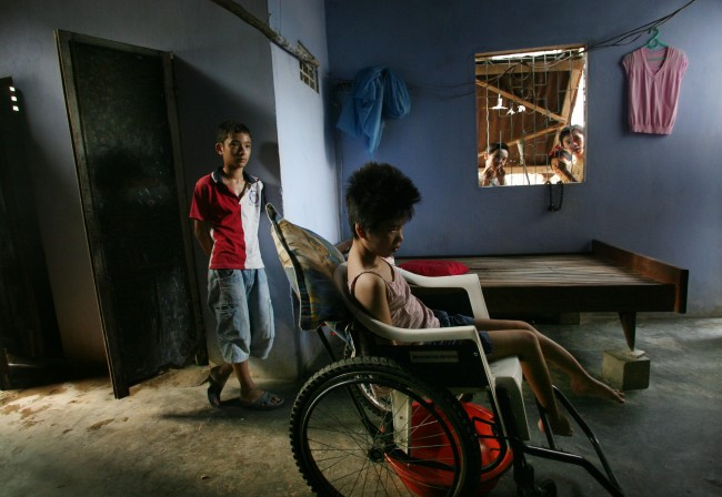 **Neighborhood children look through a window at Tran Thi Le Huyen, 23, sitting in a wheelchair in her family home in Danang, Vietnam in this May 21, 2007, file photo. The young woman has been listed by the Vietnamese government as a victim of Agent Orange contamination. Her family once lived near the highly contaminated Danang Airbase and her father was a driver for the US-backed south Vietnamese government during the war. Her family receives a small stipend and her wheelchair from the government.