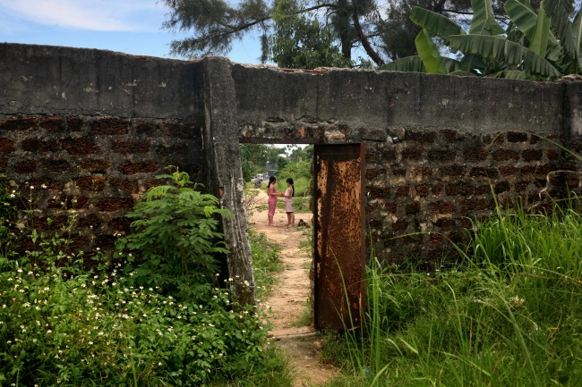 ** ONE IN A SERIES OF 15 PHOTOS BY AP PHOTOGRAPHER DAVID GUTTENFELDER WHICH WON THE APME PHOTO CONTEST FEATURE CATEGORY--FILE **Two young girls play in their village, seen through a door in the wall of the Danang airbase in Danang, Vietnam, in this May 21, 2007, file photo. More than 30 years after the Vietnam War ended, the poisonous legacy of Agent Orange has emerged anew with a scientific study that has found extraordinarily high levels of health-threatening contamination at the former U.S. air base at Danang.