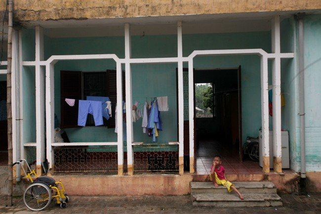 "A physically and mentally disabled child sits on the steps of a hospital ward at a ""peace village"" center in the village of Thuy An, Vietnam, which houses people suffering from illnesses and deformities associated with contact to dioxin in chemical defoliant Agent Orange, in this May 15, 2007, file photo"