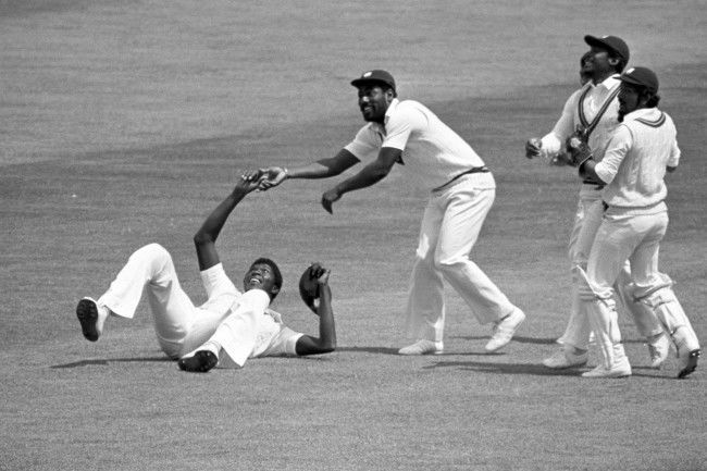 Joel Garner (on ground) gets the congratulations of Viv Richards after taking the catch - off Michael Holding's bowling - which dismissed Alan Knott for nine in England's first innings in the second Cornhill Test match at Lord's . Other West Indian players including wicket-keeper Deryck Murray (wearing pads) celebrate Knott's departure.