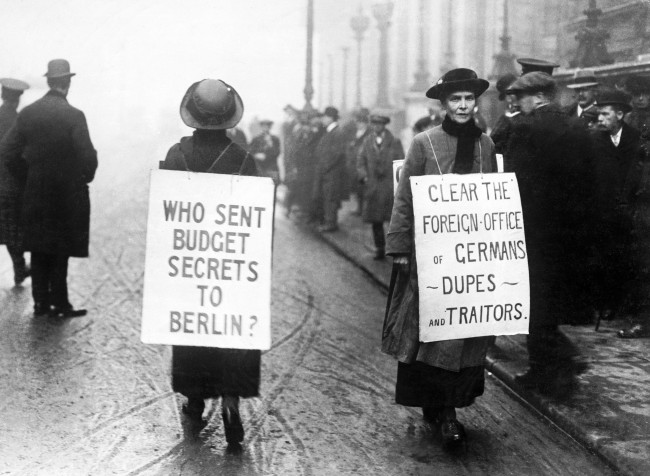 """Two patriotic women protest with sandwich boards outside the Reform Club, where a meeting of the Liberal Party was being held. The women allege that there are """"Germans, dupes and traitors"""" in the Foreign Office and that some one sold secrets regarding the annual budget to the Germans."""