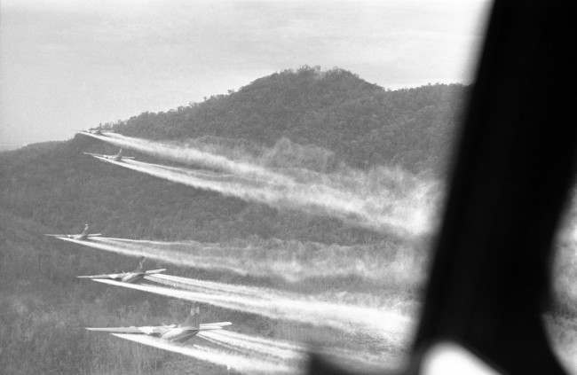 Flying a bare 100 feet above the jungle hills west of Hue, 5 bulky C-123 ?providers? cut loose with a spray of chemical defoliant on August 14, 1968. The planes are flown by U.S. air force crews who have nicknamed themselves the ?ranch hands?. The chemicals used burn off heavy foliage hiding enemy infiltrations routes and base camps. So far in Vietnam more than 4 million acres have been sprayed with the defoliant and plans call for new target areas to match the increased infiltration of North Vietnamese in to the south. The aircraft are specially equipped with huge 1,000 gallon tanks holding 11,000 lbs. of herbicide. To hit their target areas they fly barely above the tree tops and in tight formation. In particularly dangerous areas they are provided with fighter-bomber escorts.
