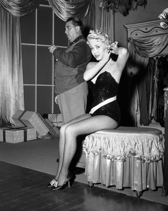 Lovely singing star Jane Powell, who used to play demure young roles shows she has more talent in ?Three Sailors and a Girl,? now being filmed in Hollywood, Los Angeles, March 29, 1953. The lovely Jane Powell is shown here readjusting an earring before doing a dazzling dance routine. Dance director LeRoy Prinz watches the chorus line (not shown) as they run through a number.