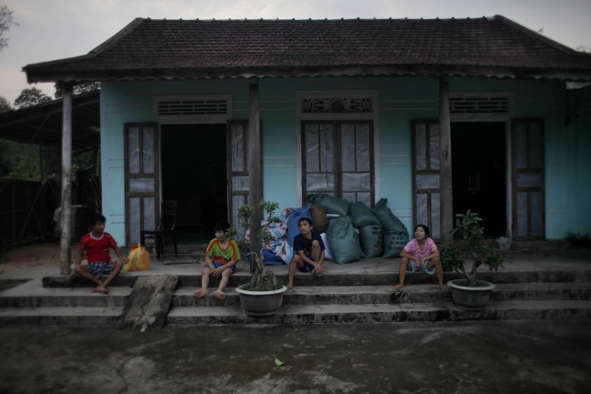 In this photo taken on Oct. 4, 2009, Vietnamese siblings, from left, Tran van Hoang, Tran Van Lam, Tran Van Luan and Tran Thi Luy, sit on the front porch of their family home in the village of Cam Tuyen, Vietnam. The siblings were born with profound physical and mental disabilities that the family, and local officials say, were caused by their parents' exposure to the chemical dioxin in the defoliant Agent Orange.