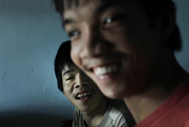 In this photo taken on Oct. 5, 2009, Tran Van Lam, left, and Tran van Hoang sit inside their family home in the village of Cam Tuyen, Vietnam. The two men were born with profound physical and mental disabilities that the family, and local officials, say were caused by their parents' exposure to the chemical dioxin in the defoliant Agent Orange.