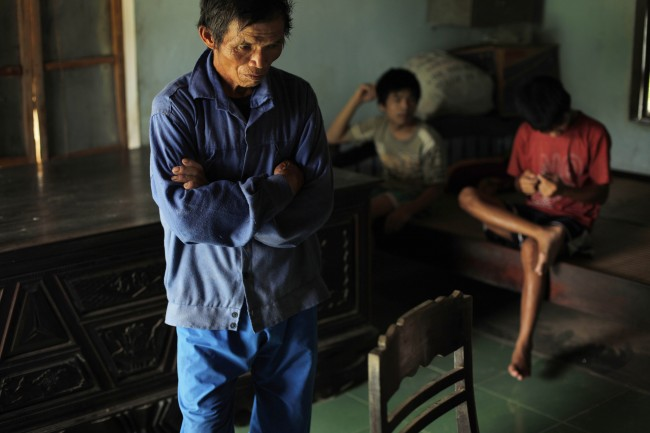 In this photo taken on Oct. 5, 2009, Tran Van Tram, 60, stands inside his home in the village of Cam Tuyen, Vietnam. Tran Van Tram and his wife have raised four children with profound physical and mental disabilities that the family, and local officials say, were caused by his parents' exposure to the chemical dioxin in the defoliant Agent Orange.