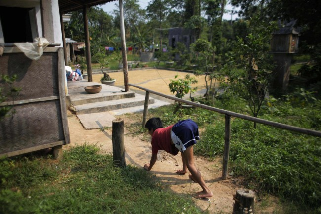 In this photo taken on Oct. 5, 2009, Tran van Hoang walks on all fours as he returns to his family home in the village of Cam Tuyen, Vietnam. The young man was born with profound physical and mental disabilities that his family, and local officials, say were caused by his parents' exposure to the chemical dioxin in the defoliant Agent Orange.