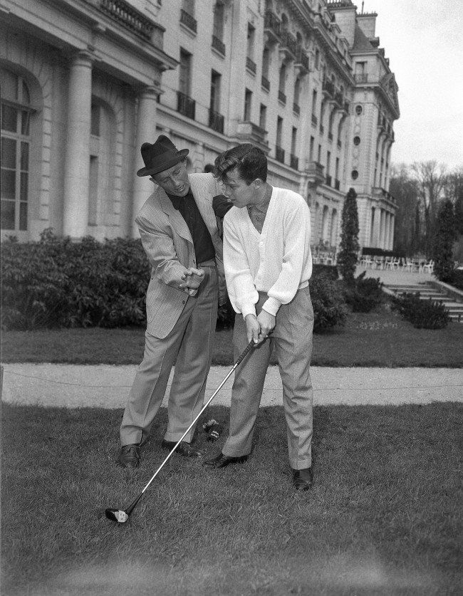 American singer Bing Cosby, who is vacationing in the Trianon Palace Hotel in Versailles, March 30, 1953, teaches his younger son Lindsay how to play golf in the gardens of the hotel.