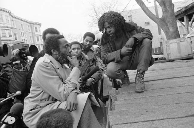 Dick Gregory, political satirist and activist, left, talks with man calling himself Phil Africa in front of the MOVE headquarters in Philadelphia's near west side, . Gregory has agreed to help mediate the long stand-off between the city and the radical organization.   Date: 10/03/1978