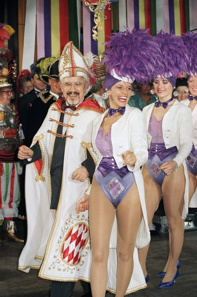 German government spokesman Hans Klein, dressed in carnival costume, left, smiles surrounded by dancers at a carnival party on February 21, 1990 at the Chancellery in Bonn, Germany.