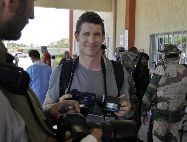 Photojournalist Tim Hetherington, center, stands with other photographers outside the entrance to the hospital in Ajdabiya, Libya Sunday, April 10, 2011. Hetherington was killed in Misrata, Libya Wednesday, April 20, 2011 while covering battles between Libyan rebels and government forces. (AP Photo/Ben Curtis) Date: 10/04/2011