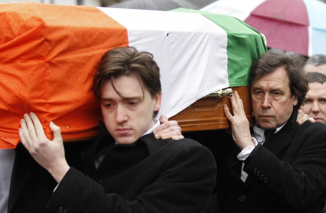 The actor Stephen Rea, right, carries the coffin of his ex-wife, Dolours Price at her funeral in west Belfast, Northern Ireland, Monday, January, 28, 2013. Price, an Irish Republican Army veteran who accused Sinn Fein party chief Gerry Adams of involvement in IRA killings and bombings died on Wednesday, at her home in Malahide, north of Dublin, and was possibly the result of a drug overdose and foul play was not suspected. But it could have implications as far away as the U.S. Supreme Court. In interviews Price repeatedly described Adams as her IRA commander in Catholic west Belfast in the early 1970s when the outlawed group was secretly abducting, executing and burying more than a dozen suspected informers in unmarked graves. Adams rejects the charges. Since 2011 Northern Ireland's police have been fighting a legal battle with Boston College to secure audiotaped interviews with Price detailing her IRA career to see if they contain evidence relating to unsolved crimes, particularly the 1972 kidnapping and murder of a Belfast widow, Jean McConville. Price allegedly admitted being the IRA member who drove McConville across the Irish border to an IRA execution squad. (AP Photo/Peter Morrison) Ref #: PA.15656637  Date: 28/01/2013
