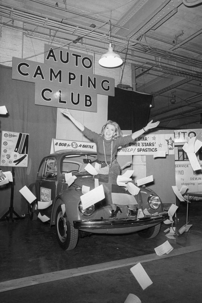 Actress Susan Hampshire in a flurry of raffle tickets at Colex ' 70, the 12th annual Camping and Outdoor Life and Travel Exhibition which opened at Olympia, London. Susan is seated on the bonnet of the new Volkswagon Beetle, which is first prize in a raffle organised by the Eastern Centre of the Volkswagon Owner's Club in conjunction with the Stars Organisation for Spastics. The raffle tickets were sold by the actress. Archive-pa143437-2 Ref #: PA.16531927  Date: 31/12/1969
