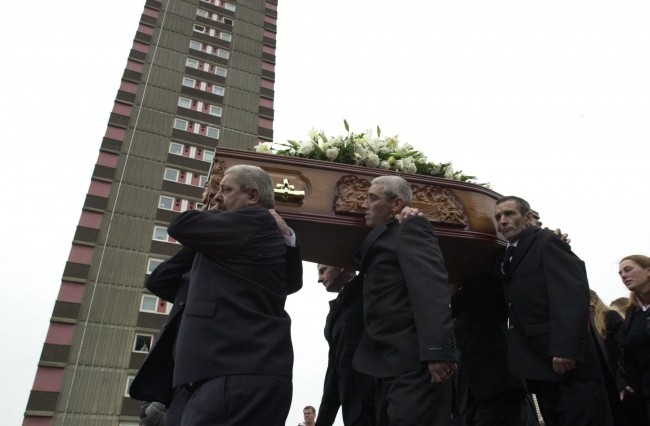 Jean McConville's coffin is caried past the Divis Flats, Falls Road, Belfast, Northern Ireland, where she was abducted by the IRA in 1974, after her funerl at St. Paul's Church, Falls Road, Belfast, Northern Ireland. Mrs McConville was killed by the IRA in 1974, her body only being discovered on a beach near Dundalk in Ireland earlier this year.  Ref #: PA.1824492  Date: 30/10/2003