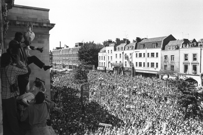 housands of football fans watch Arsenal midfielder David Rocastle does a victory dance on the balcony of Islington Town Hall during the Gunners homecoming parade. Rocastle holds the traditional League Championship trophy, won by Arsenal with a thrilling 2-0 victory over Liverpool.