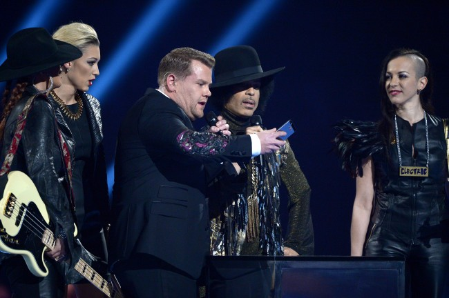 Host James Corden, centre, takes a picture onstage with US recording artist Prince during at the BRIT Awards 2014 at the O2 Arena in London on Wednesday, Feb. 19, 2014.