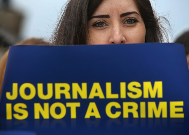 Lebanese journalist holds a placard, to show her solidarity with detained journalists by Egyptian authorities during a sit-in, at the Martyrs square in downtown Beirut, Lebanon, Thursday, Feb. 27, 2014. Journalists and their supporters across the globe are protesting the detention of four Al Jazeera staffers in Egypt. From London's Trafalgar Square and Lebanon's Martyrs' Square, media workers and free speech advocates gathered with masking tape stuck across their mouths. Peter Greste, Mohammed Fahmy, Baher Mohamed, and Abdullah Al Shamy, are among 20 defendants being tried on charges of belonging to and aiding a terrorist organization for their coverage of the Muslim Brotherhood. (AP Photo/Hussein Malla)