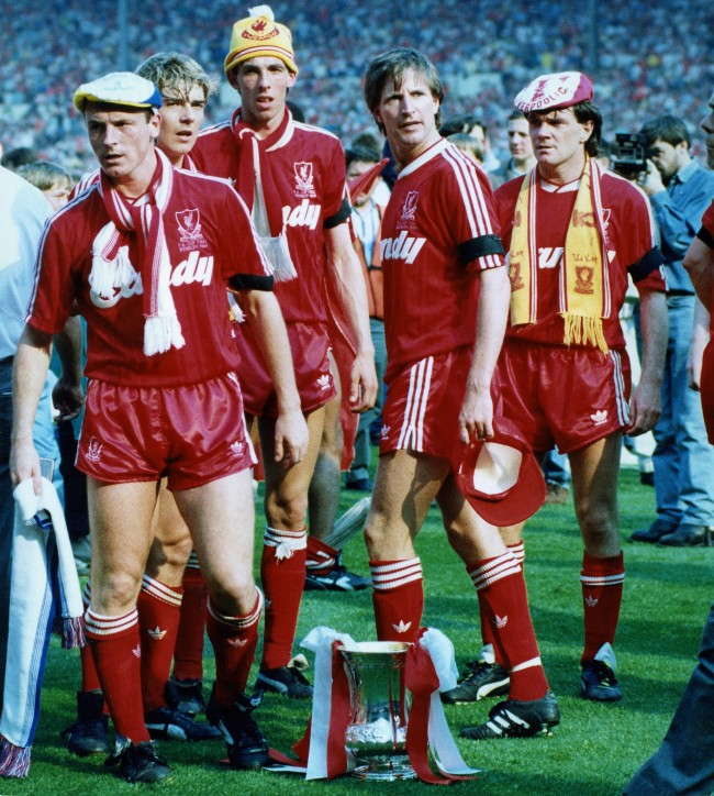 FA Cup winners stand dejectedly around the trophy, sitting on the ground, when the team was prevented from lining up for the official team photograph, by a pitch invasion, at Wembley, London, on May 20, 1989. From left to right; Steve McMahon, Barry Venison, Gary Ablett, Ronnie Whelan and Ray Houghton. Perimeter fencing had been removed from the ground after last month's Hillsborough stadium tragedy in which 95 Liverpool fans died. As a mark of respect both teams wore black armbands. (AP Photo/White)