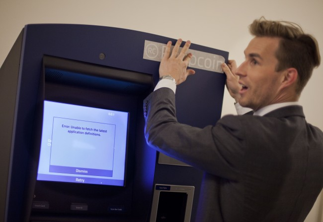 Robocoin CEO Jordan Kelly, places the company's decal on the Robocoin machine, the world's first bitcoin kiosk (ATM) for buying and selling popular and controversial digital currency, before a demonstration on Capitol Hill in Washington, Tuesday, April 8, 2014. (AP Photo/Pablo Martinez Monsivais) Date: 08/04/2014