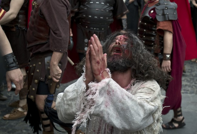 A man performs during a reenactment of the crucifixion of Jesus Christ in the old city district of Bucharest, Romania, Tuesday, April 15, 2014.